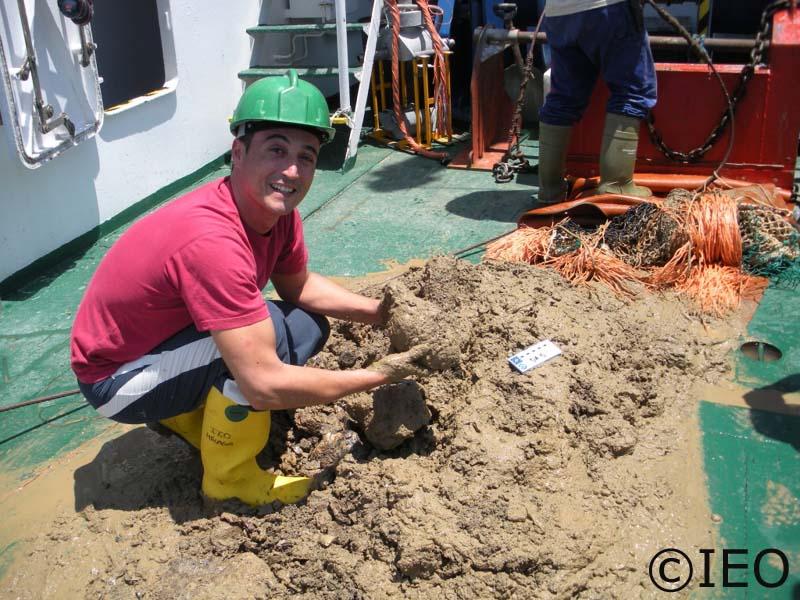 Curro López sobre el material recogido por la draga de arrastre bentónica, sostiene sobre sus manos una chimenea carbonatada autigénica, producto de la actividad bacteriana en el consumo de metano ©IEO