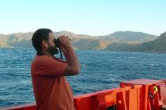 Beneharo Rodríguez, miembro de SEO BirdLife, observando las aves que pasan cerca del barco / Beneharo Rodríguez, member of the SEO BirdLife organization, is watching the birds passing next to the boat ©ICM-CSIC
