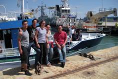 Foto de familia al finalizar la primera parte de la campaña. Los científicos en el muelle, los tripulantes a bordo del barco en el momento de salir a la mar camino de Huelva ©IEO